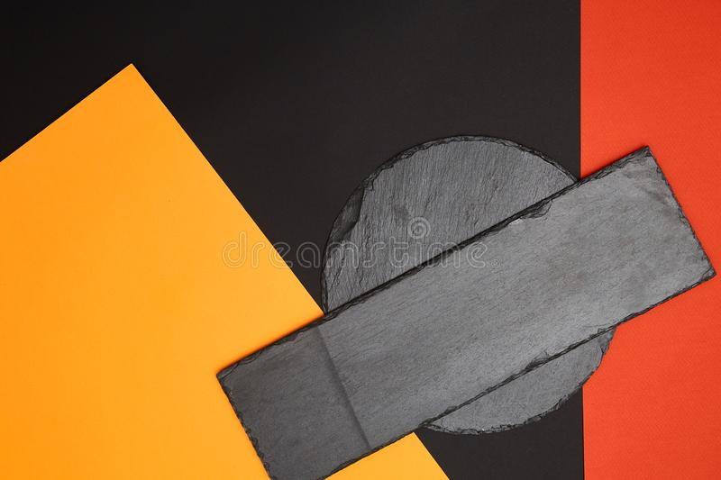 Composition of empty black slate serving board on multicolored background with geometric composition.  royalty free stock images