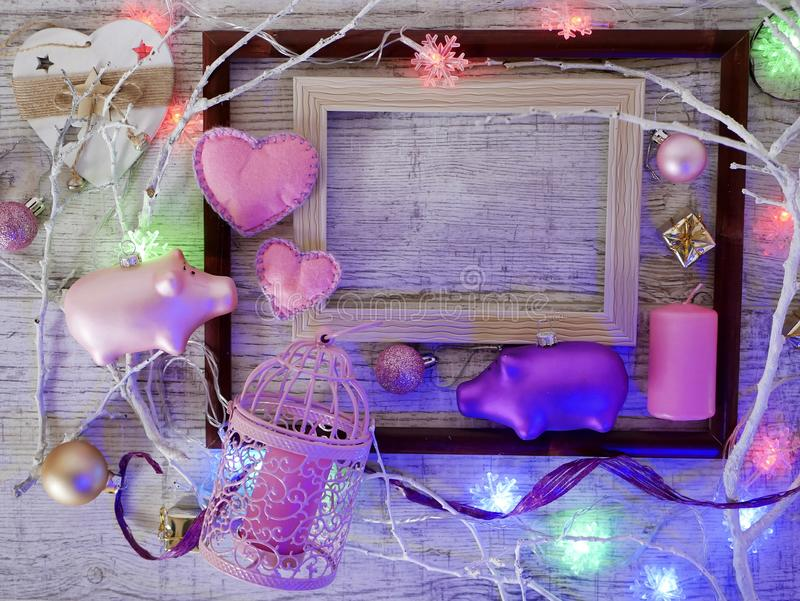 Composition of empty frames, Christmas decor, a pair of pigs, felt hearts, candles, illuminations, pink coloring royalty free stock images