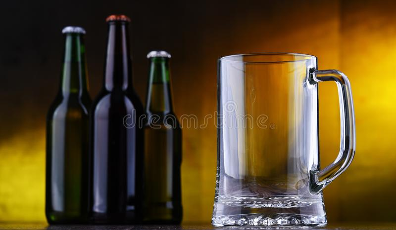 Composition with empty glass and bottles of beer.  stock image