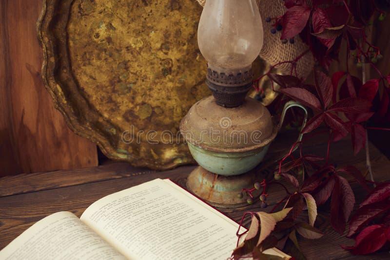 Composition en automne avec une vieille lampe de kérosène, un vieux plateau et des feuilles ouvertes de raisin de livre et rouge  photographie stock libre de droits