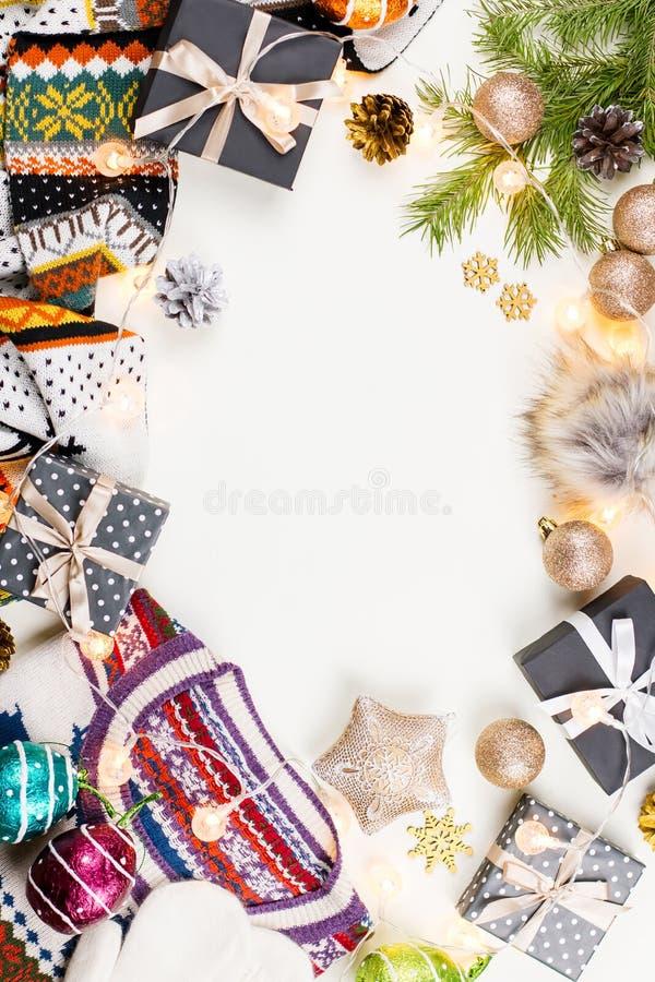 Composition en humeur de Noël avec le chandail, le chapeau, les présents et les lumières de Noël Configuration plate de concept d photos stock
