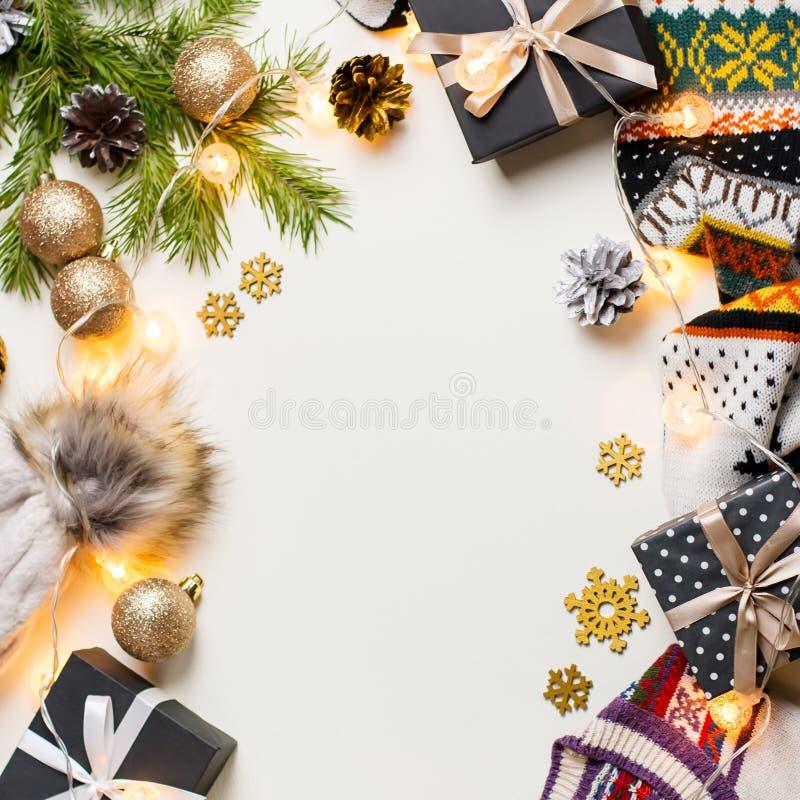 Composition en humeur de Noël avec le chandail, le chapeau, les présents et les lumières de Noël Configuration plate de concept d images libres de droits