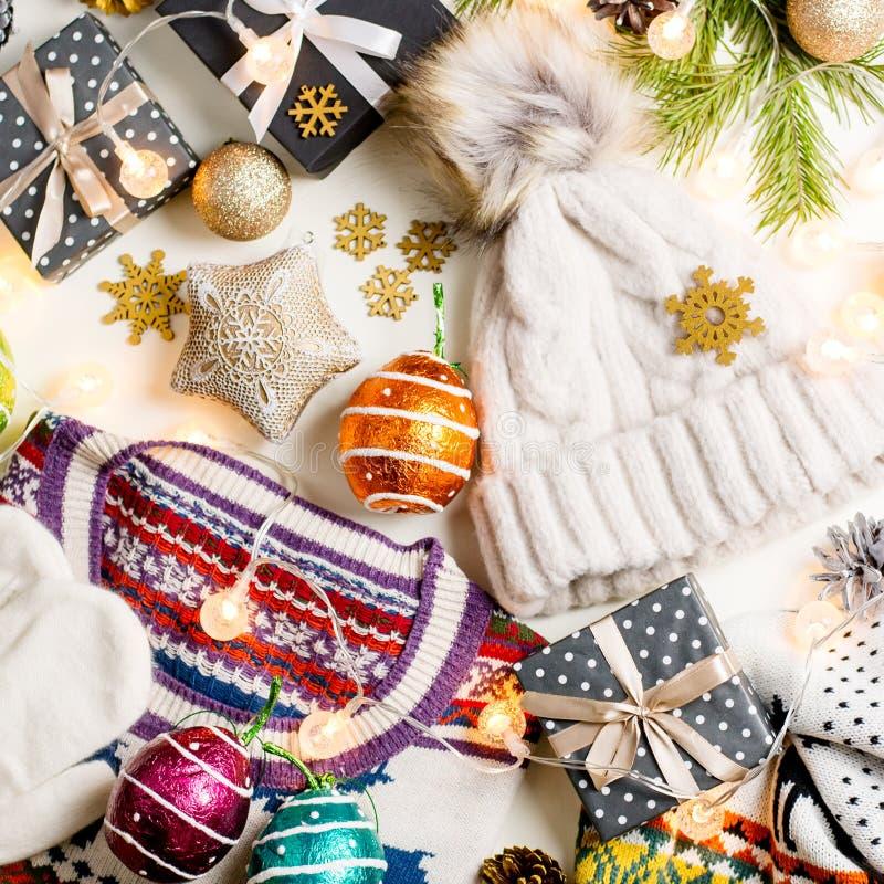 Composition en humeur de Noël avec le chandail, le chapeau, les présents et les lumières de Noël Configuration plate de concept d photos libres de droits