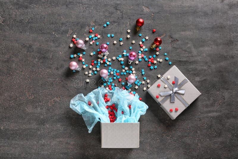 Composition en Noël avec le boîte-cadeau ouvert sur le fond gris photographie stock