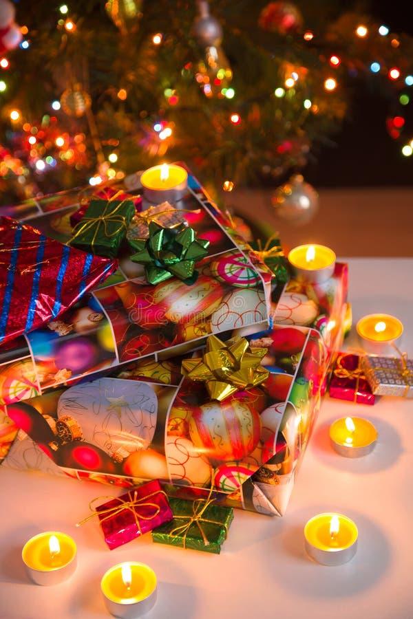 Composition en nouvelle année et en Noël : boîte-cadeau et bougies brûlantes sous l'arbre de Noël, vertical photo stock