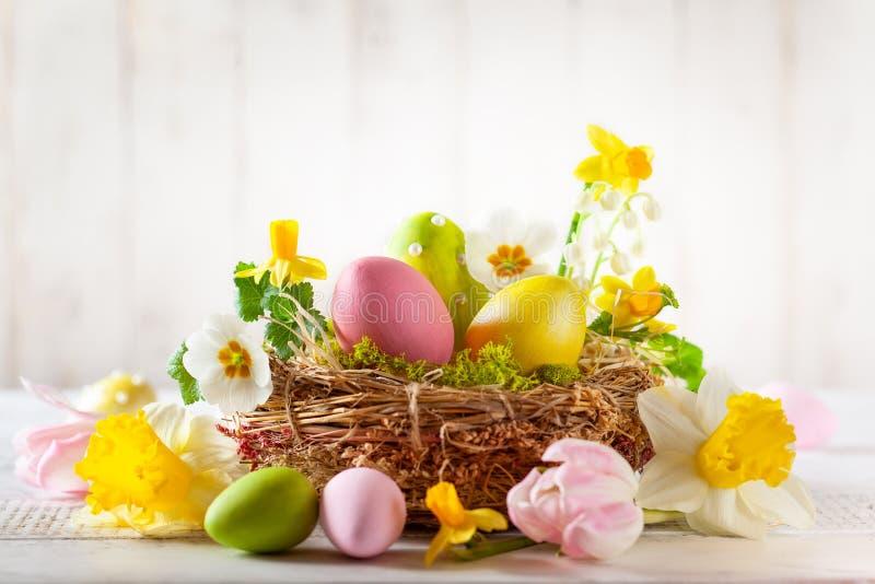 Composition en Pâques avec des oeufs de pâques dans le nid, les fleurs de ressort et les branches des saules de chat images libres de droits