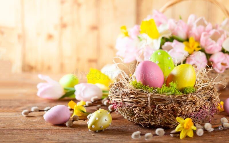 Composition en Pâques avec des oeufs de pâques dans le nid, les fleurs de ressort et les branches des saules de chat image libre de droits