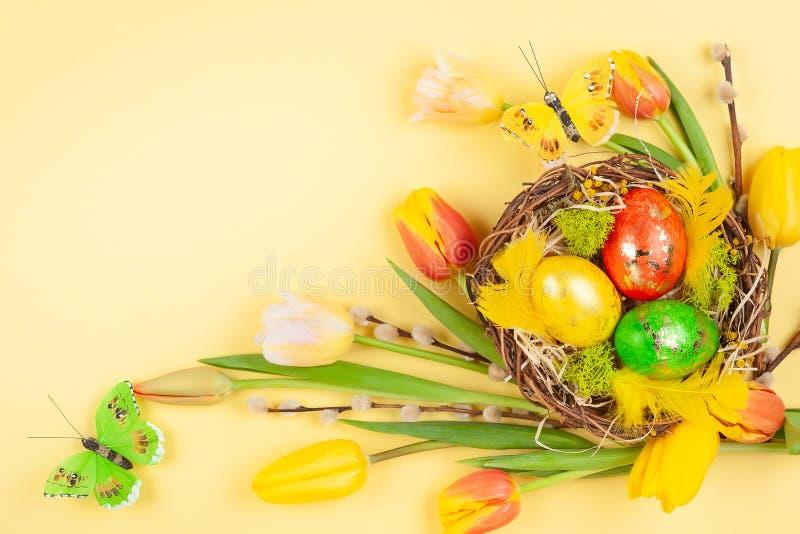 Composition en Pâques avec des oeufs de pâques en fleurs de nid et de ressort photo stock