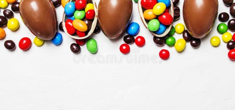 Composition en Pâques avec les oeufs de chocolat et la sucrerie colorée, blancs image stock