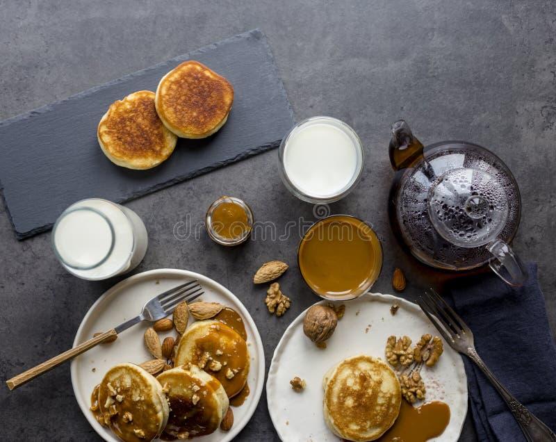 Composition en petit déjeuner avec les crêpes, le lait et le thé au fond noir photo stock