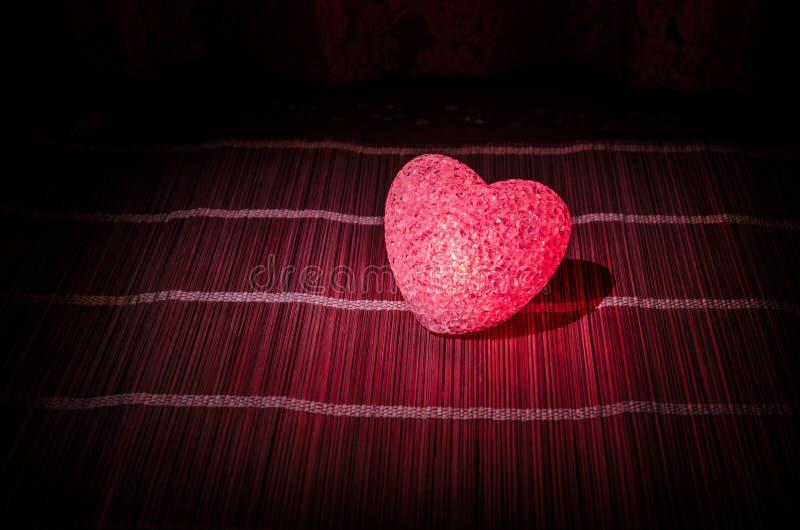 Composition en Saint-Valentin avec le bonbon brûlant le coeur multicolore sur le fond foncé, le centre sélectif, ou la carte de v image libre de droits