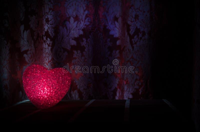 Composition en Saint-Valentin avec le bonbon brûlant le coeur multicolore sur le fond foncé, le centre sélectif, ou la carte de v image stock