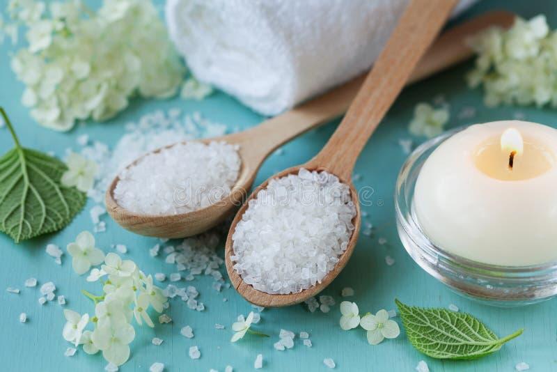 Composition en station thermale avec du sel de mer dans la cuillère en bois, la serviette de bain, les fleurs blanches et les bou photo libre de droits