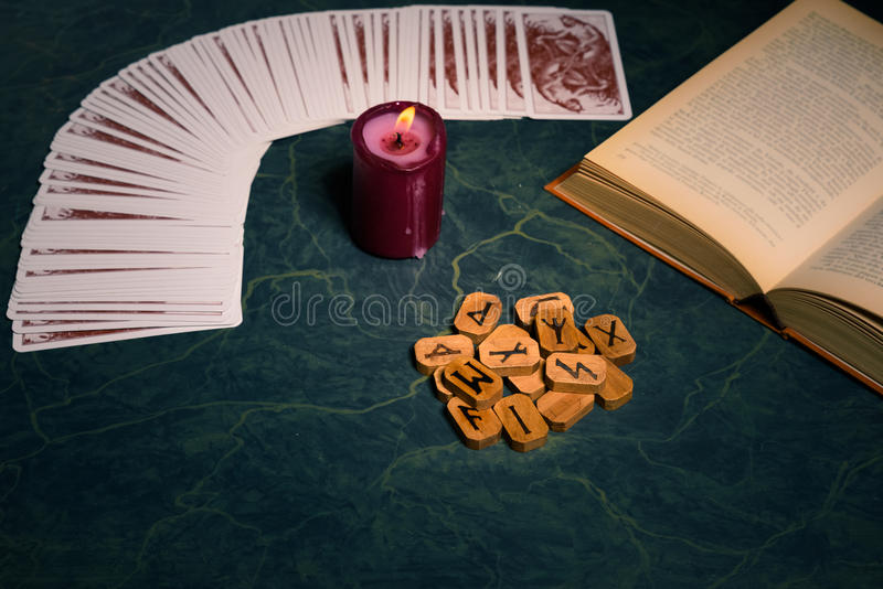 Composition of esoteric object. S,candle,Cards,book and wooden runes used for healing and fortune-telling,on green background,vintage style royalty free stock images