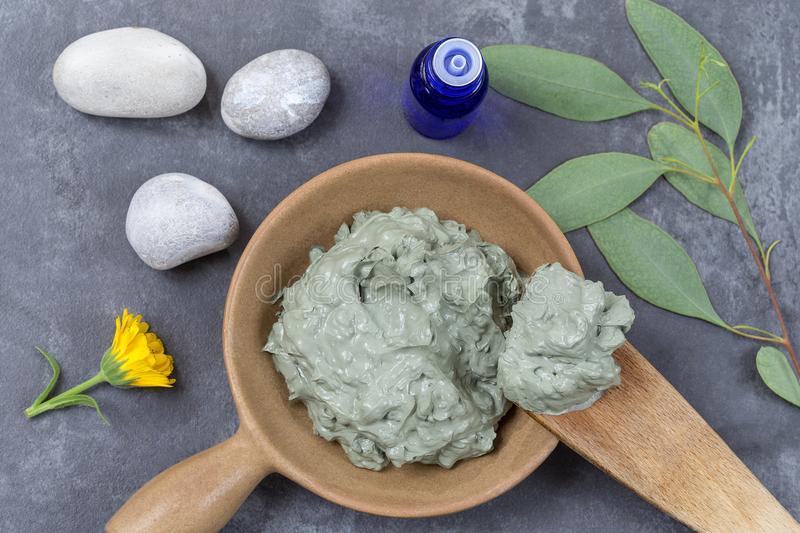 Essential oil with cosmetic clay and cornflower and branch of eucalyptus, stones, for spa treatments, in wood spoon, on stock photo