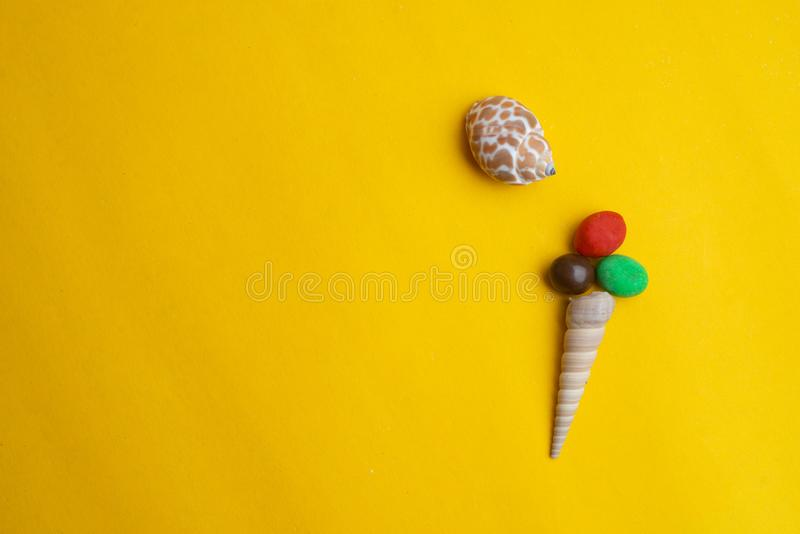 Composition of exotic sea shells on a yellow background. Ice cream concept royalty free stock photos