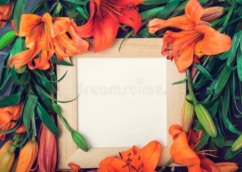 Composition exotique de fleurs La guirlande faite en lis orange fleurit avec le cadre en bois carré et la carte vierge de papier  photographie stock