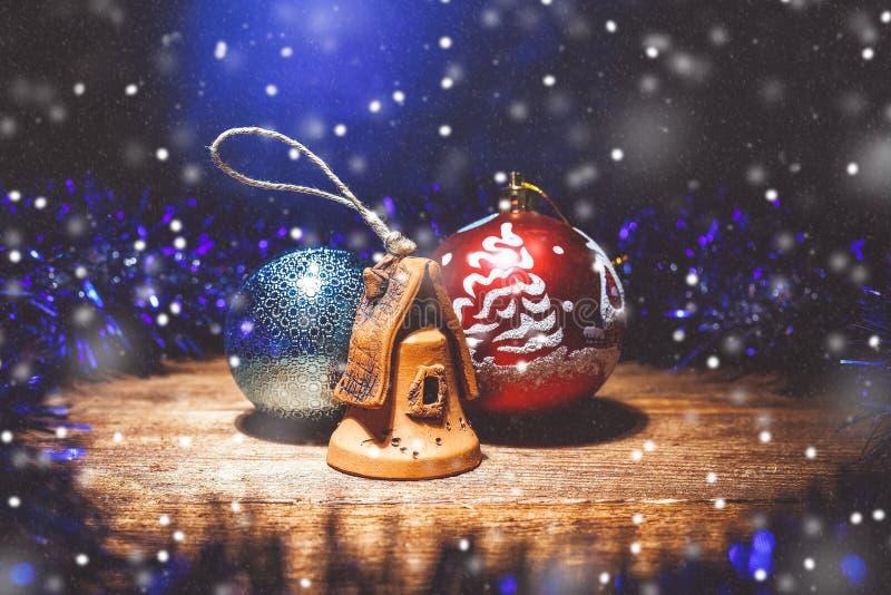 Composition féerique de Noël des décorations de Noël : deux boules et une maison d'argile sous la neige artificielle images libres de droits