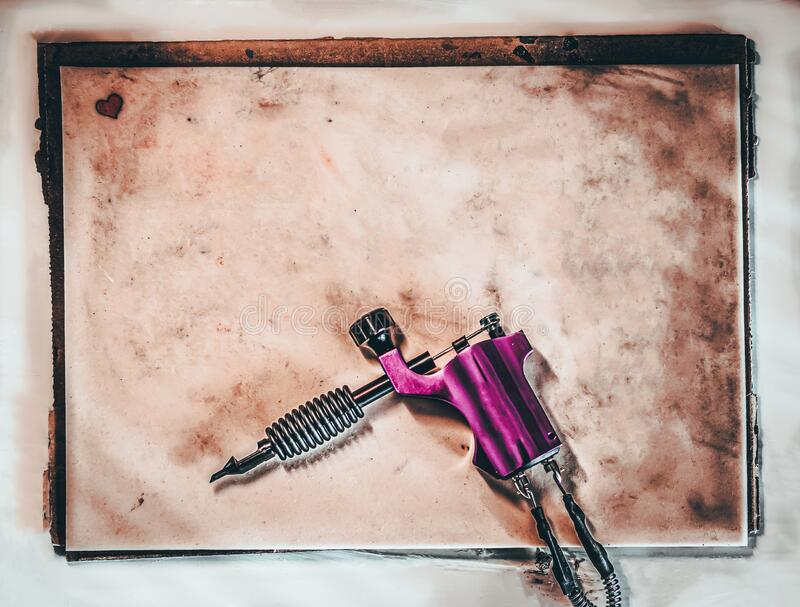 Composition with fake leather for tattooing, empty, to add a text, dirty with ink,. With a small heart tattooed in the corner, and a pink tattoo machine royalty free stock photo