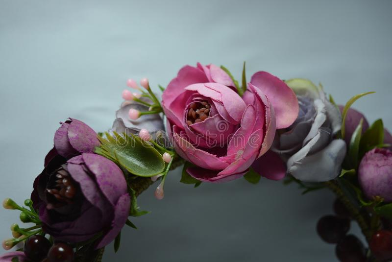 The composition of fashion from flowers of purple and pink color with green leaves and berries made of cloth stock photo