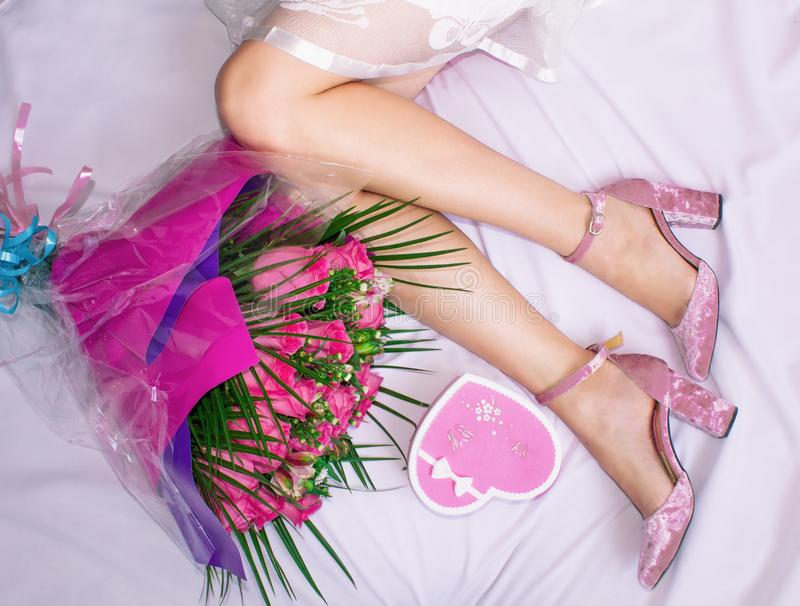 Composition, female feet on a sheet, a bouquet of roses and a box in the form of a heart with a gift. stock photography