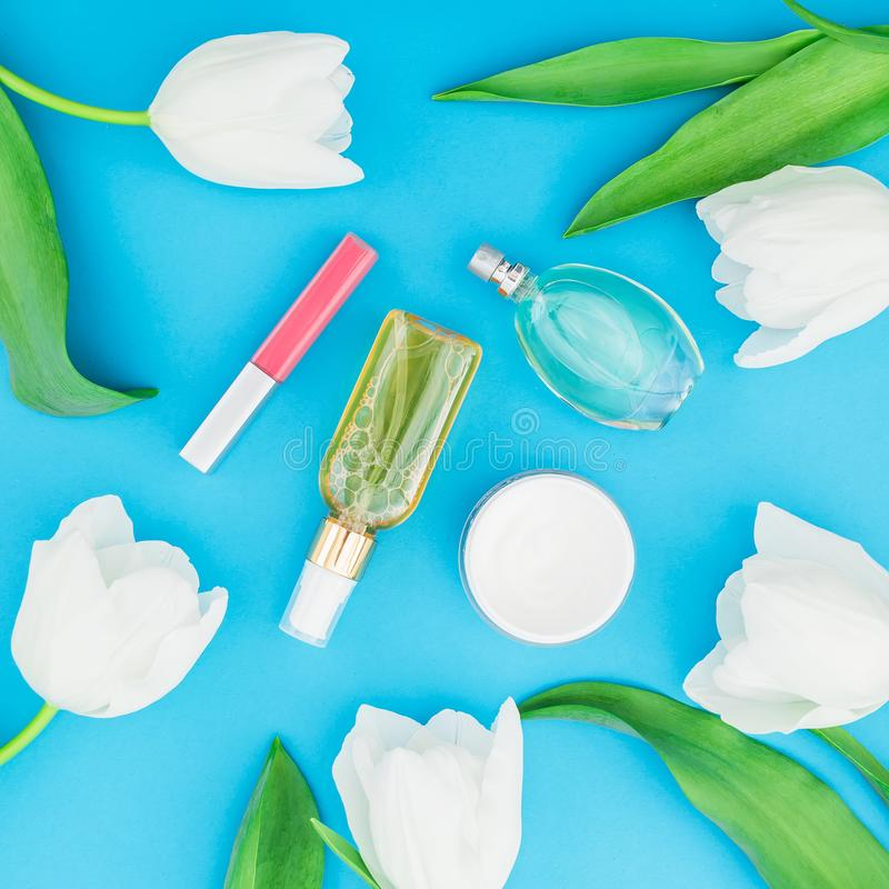 Composition with feminine perfume, pink lipstick, face cream and white tulips flowers on blue background. Beauty blog. Flat lay, t stock photography