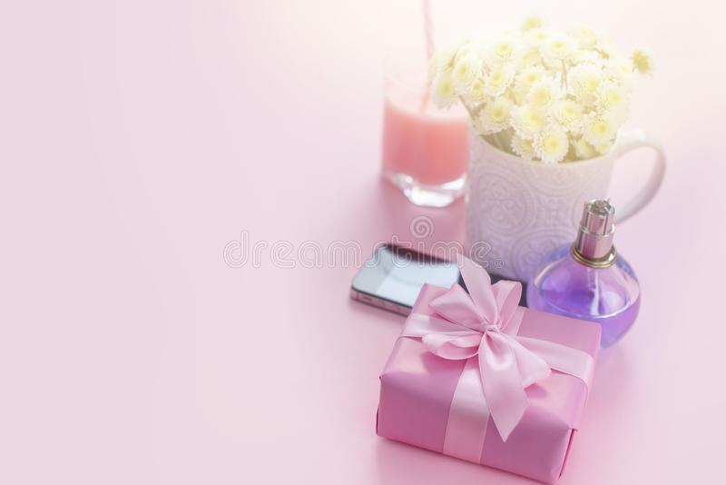 Composition flat lay gift to a woman Modern gadget mobile phone glass cocktail perfume bouquet of flowers Preparing for the holida stock image