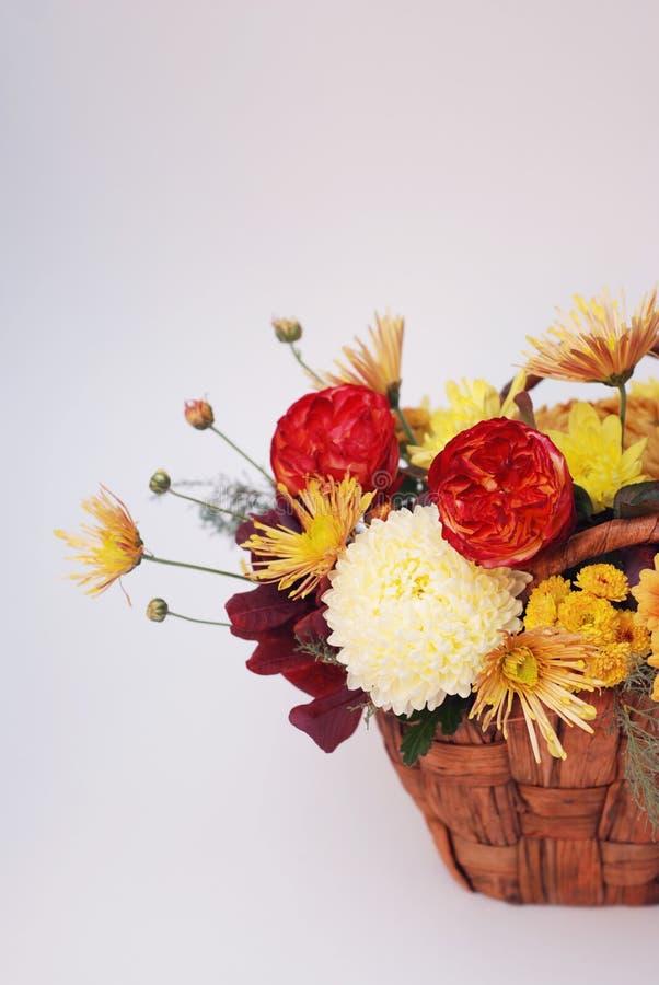 Composition florale avec des oeillets et des marguerites de couleur de chute dans le panier Disposition verticale images stock