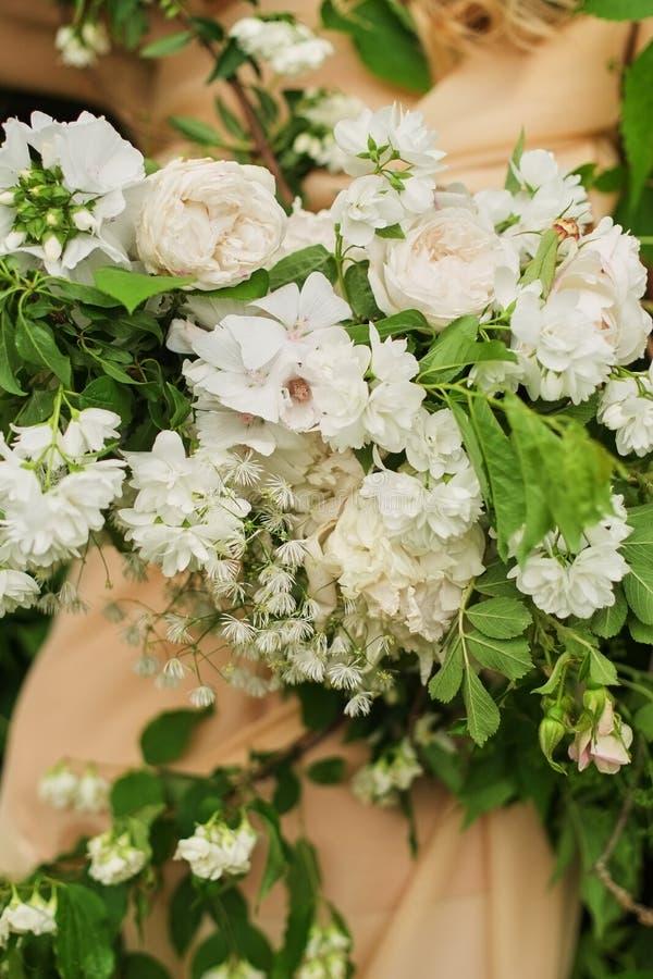 Composition florale des fleurs blanches sur la robe la jeune mariée tient un plan rapproché l'épousant de bouquet images libres de droits
