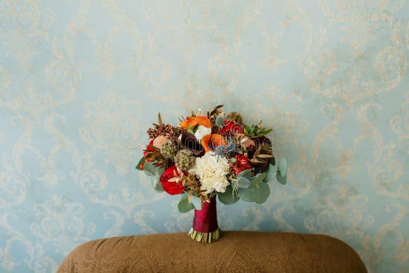 Composition florale pour une noce Le bouquet des roses roses, des pivoines rouges, et d'autres fleurs sur le mur bleu images stock