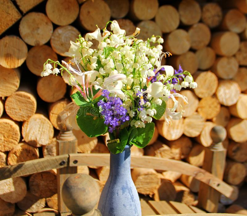 Composition of flowers, lilies of the valley and other flowers. Purple, in a vase on a background of round wooden slices stock photo
