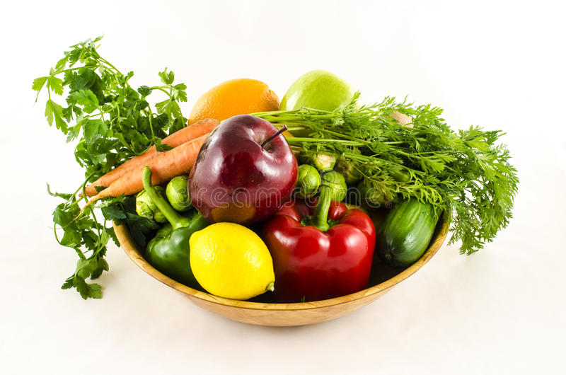 Composition of fresh fruits and vegetables in wooden bowl royalty free stock photography