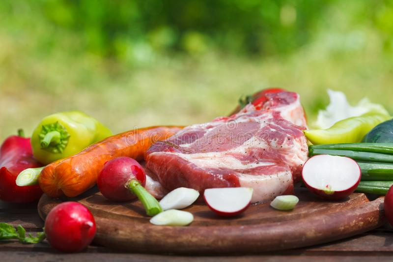 Composition of fresh healthy various vegetables and raw meat steak. Outdoor image, green nature in background stock photo