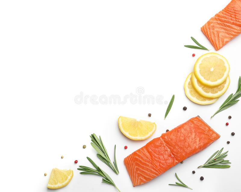 Composition with fresh raw salmon fillets on white background. Space for text. Composition with fresh raw salmon fillets on white background, top view. Space for stock photo