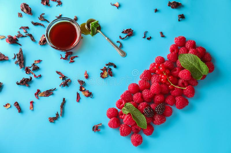 Composition with fresh ripe berries and honey on color background stock photography