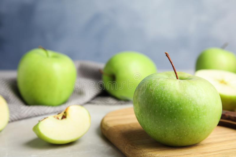 Composition with fresh ripe green apple on wooden board against blue background. Space for text. Composition with fresh ripe green apple on wooden board against royalty free stock images