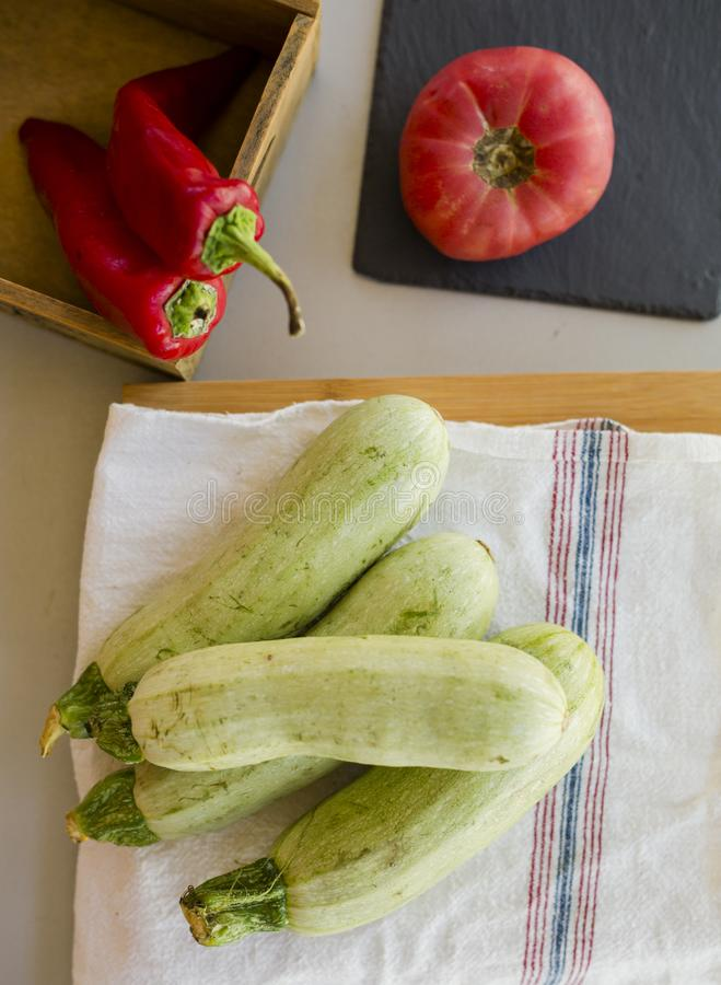 Composition of fresh ripe zucchini with hot red chili peppers and tomato stock photo