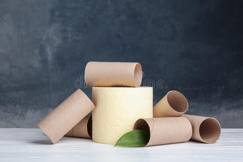 Composition with full and empty toilet paper rolls. On table stock photography