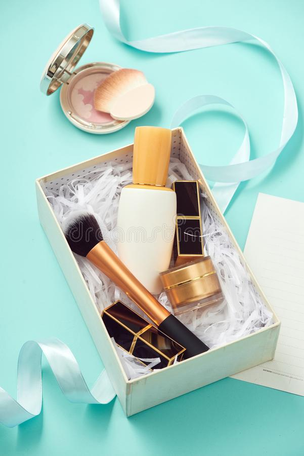 Composition with gift box and set of decorative cosmetics. On blue background royalty free stock photography