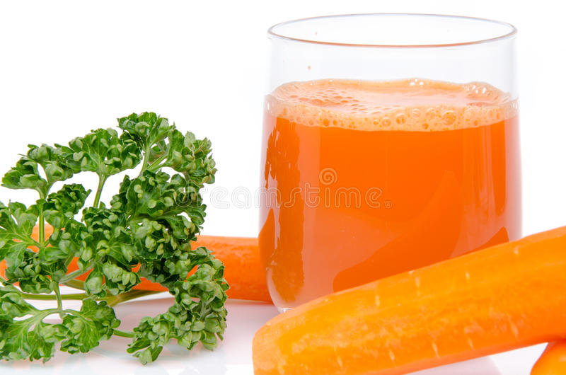 Composition with a glass of carrot juice, fresh carrots and pars royalty free stock images