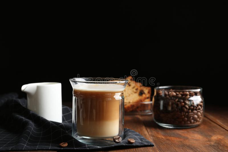 Composition with glass of delicious coffee drink on wooden table against black background. Space for text stock images