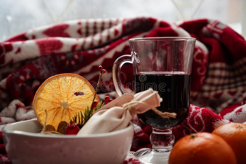 Composition with a glass of hot mulled red wine with spices, oranges, tangerines and a blanket. stock photography