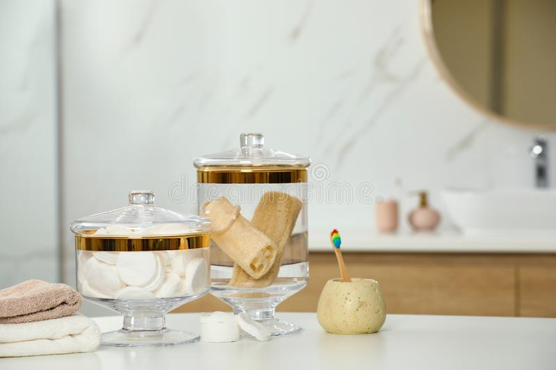 Composition of glass jar with cotton pads and sponges on table in bathroom. Space for text. Composition of glass jar with cotton pads and luffa sponges on table royalty free stock image