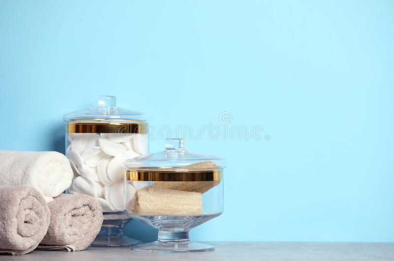 Composition of glass jar with cotton pads on table near blue wall. Space for text stock images