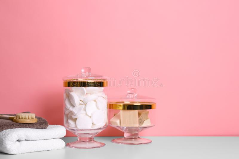 Composition of glass jar with cotton pads on table near pink wall. Space for text royalty free stock photo
