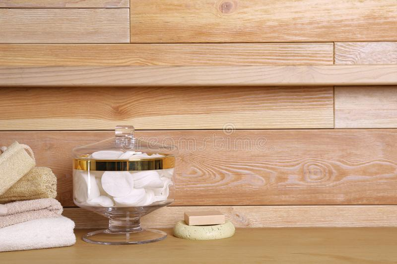 Composition of glass jar with cotton pads on table near wooden wall. Space for text royalty free stock photos
