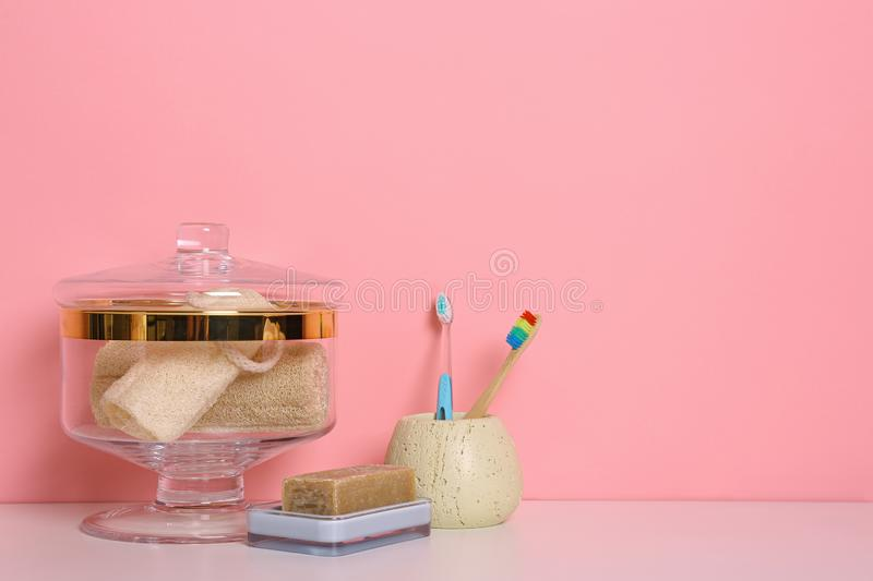 Composition of glass jar with luffa sponges on table near pink wall. Space for text stock photography
