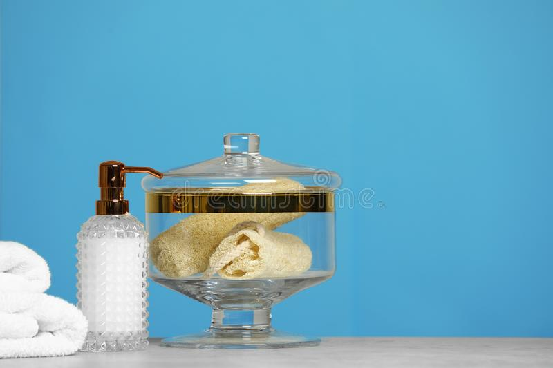 Composition of glass jar with luffa sponges on table near pink wall. Space for text royalty free stock photo