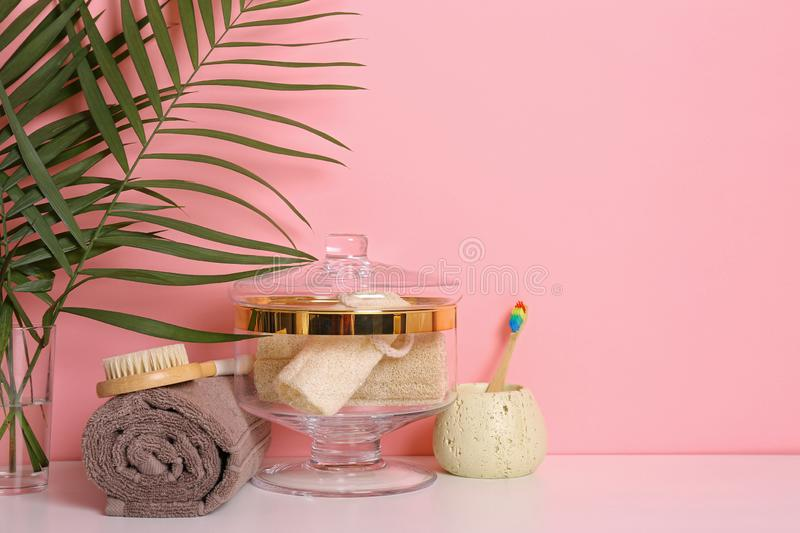 Composition of glass jar  luffa sponges on table near pink wall. Space for text. Composition of glass jar with luffa sponges on table near pink wall. Space for royalty free stock photo
