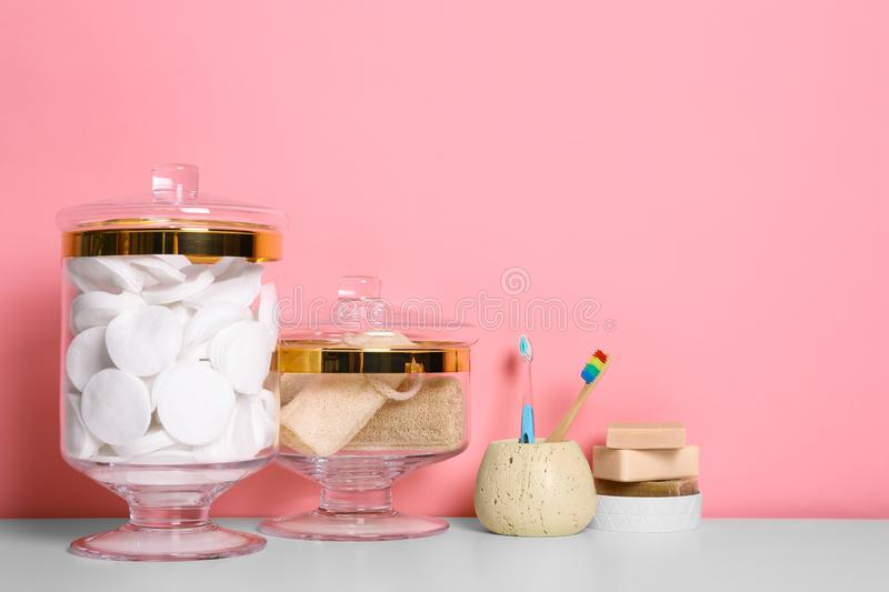 Composition of glass jar with  pads on table near pink wall. Space for text. Composition of glass jar with cotton pads on table near pink wall. Space for text royalty free stock images